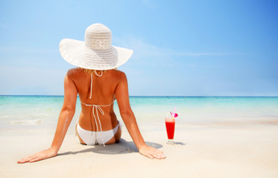 Attractive woman wearing a hat on the beach against sky.